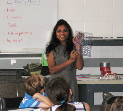 woman teaching young students