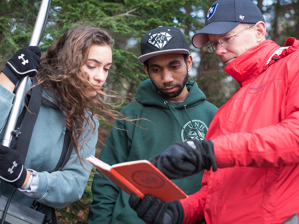 two students and a professor conductiong research outdoors