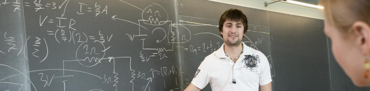 Grad student teaching a class in front of a blackboard
